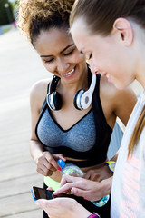 Two fit and sporty young women using mobile phone in the park.