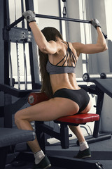Young sexy fitness woman workout with training machine in the gym