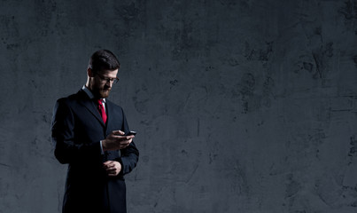 Businessman standing with smartphone over dark wall background. Business, career job concept.