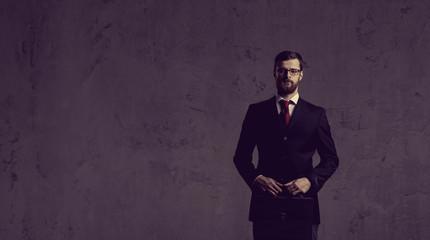Businessman standing over dark wall background. Business, career job concept.