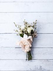 blumenstrauß mit Geschenkanhänger auf weißen Holzdielen