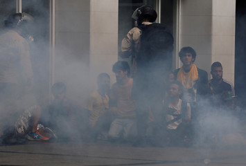 Police detain protesters behind a cloud of tear gas during a rally against Venezuela's President Nicolas Maduro's government in Caracas