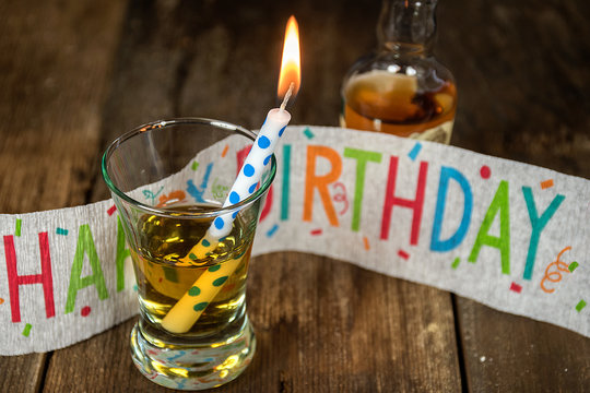 birthday candle and whiskey in shot glass on rustic wood with banner