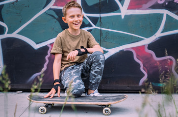 Smiling boy with skateboard sits near grafity painted wall