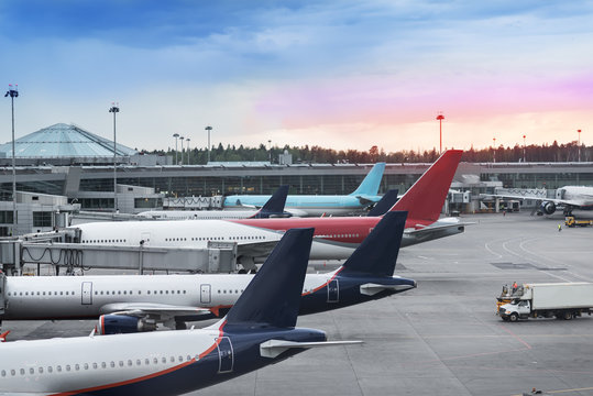 Tails of some airplanes at airport during boarding operations. They are four planes on a sunny evening, with a blue red sky. Travel and transportation concepts.