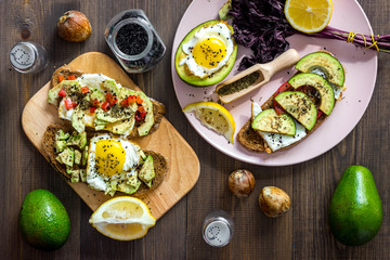 Sandwiches for breakfast with avocado, fried eggs and lemon juice on wooden table top view