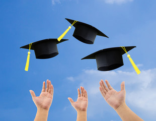 Students throwing graduation hats in the air celebrating on sky background