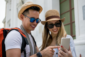 Young tourist couple looking at a selfie on the smartphone