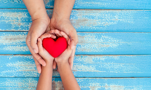 Red heart in child kid and mother hands on old blue wooden table in vintage retro style