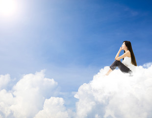 young woman  sitting on cloud and dreaming concept