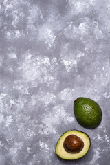 Whole and sliced green avocado
