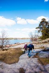Children walk along the lake shore in spring