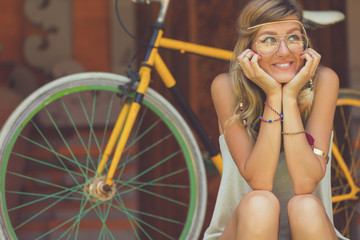 Pretty fashionable attractive woman sitting with old bicycle outdoors.