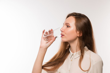 Young girl drinks clean water from a glass