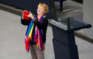 Mechthild Rawert of the SPD Party makes a picture with her phone as she attends a session of the lower house of parliament Bundestag to vote on legalising same-sex marriage, in Berlin