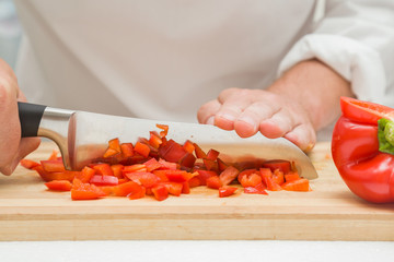 Chef's hands with knife cutting sweet paprika on the wooden board. Preparation for cooking. Healthy eating and lifestyle.