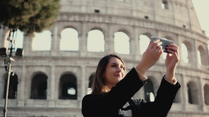 Young beautiful woman takes the selfie on smartphone. Woman walking in Rome, Italy near the Colosseum.