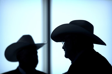 Attendees wearing cowboy hats are silhouetted as they wait for the start of an event to celebrate the re-introduction of American beef imports to China