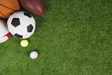 top view of balls for soccer, basketball, tennis, baseball and american football on grass pitch