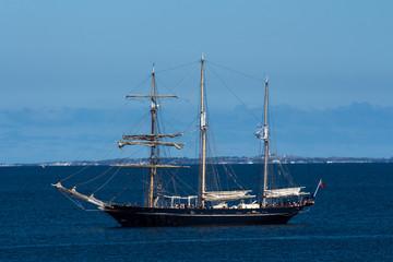 Schooner sailing ship boat moored in ocean bay against blue sky