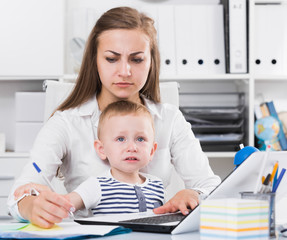 Serious mom with child is сoncentratedly working behind laptop