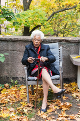 Full length of senior woman holding walking cane while sitting on chair in park