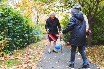 Full length of senior woman and great grandson playing with ball on footpath at park