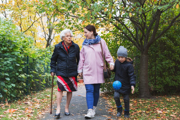 Full length of senior woman walking with daughter and great grandson in park