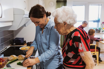 Side view of senior woman looking at daughter cutting zucchini in kitchen