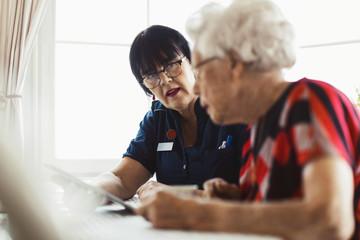 Caretaker assisting senior woman in using digital tablet at home