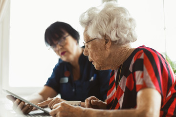 Senior woman using digital tablet with caretaker at home