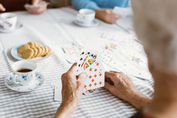Cropped image of senior woman playing cards with family at table
