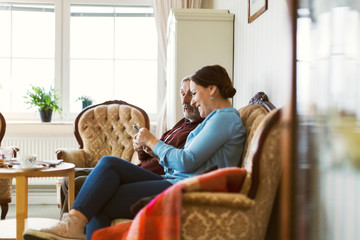 Side view of senior man using smart phone with daughter in living room