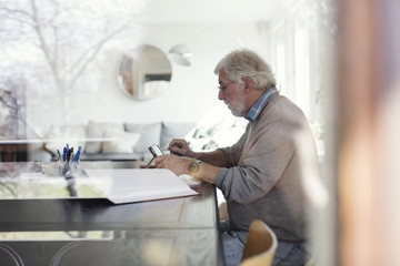 Side view of senior man using digital tablet while doing paperwork seen through glass