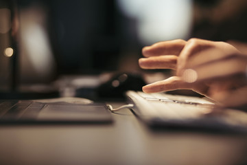 Cropped image of businesswoman using computer keyboard at desk in office