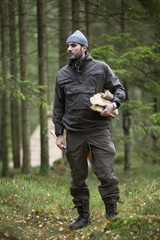 Full length of man holding firewood while standing in forest