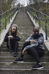 Full length of multi-ethnic couple checking wristwatch and mobile phone while sitting on steps