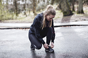 Full length of female athlete tying shoelace while crouching on wet road in forest