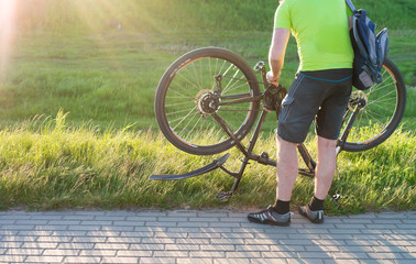 cyclist standing with a bicycle. Bicycle repair during a walk