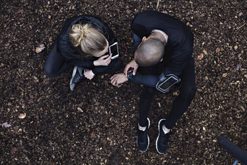 Directly above shot of couple using technologies while exercising in forest