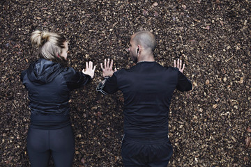 Directly above shot of couple doing plank exercise in forest