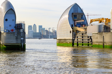 Thames Barrier in London with Canary Wharf in the background