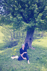 Smiling man traveler, barefoot relaxes on the green meadow