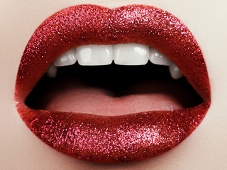 Glamour fashion bright red lips make-up with glitter. Macro of woman's face part. Sexy glossy lip makeup, luxury lady