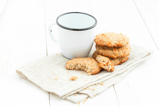 .A stack of cookies and a cup on a light wooden table on white background close up.