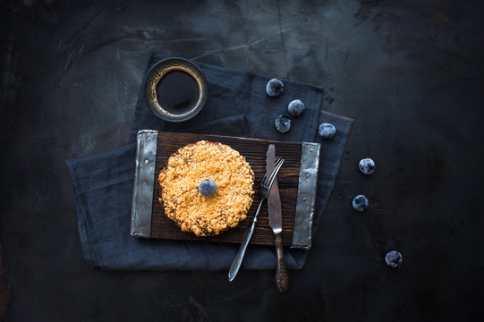Pie with plums on a board, frozen plums and a cup of coffee, knife and fork on a dark metallic background.