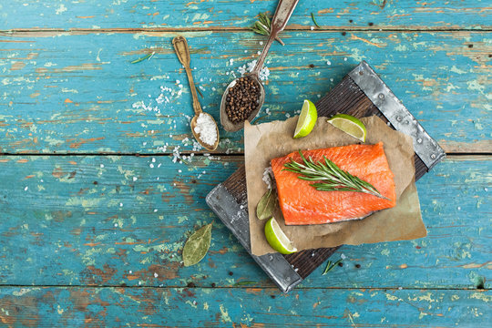 A piece of raw salmon on brown wooden board, spices, spoons, lime on the old shabby blue table, top view. Preparation for cooking fish food. Salmon steak.