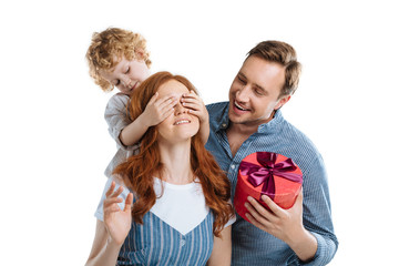 Cheerful man with adorable little son presenting gift box to happy young woman isolated on white
