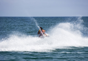 Happy young couple riding jet ski in speed on sea