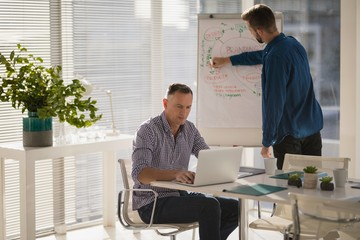 Male executive using laptop while coworker writing on flip chart